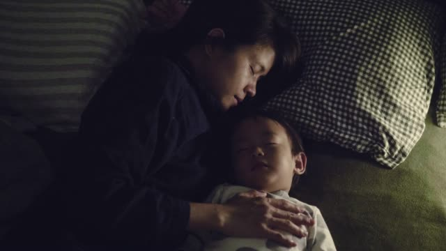 Asian Mother At Home With Sleeping Her Baby Boy At Night
