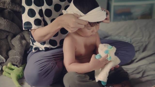 vídeos y material grabado en eventos de stock de asia madre cambiarse de ropa a su bebé en la cama - cambiar pañal