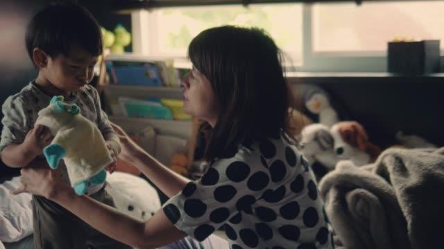 Aziatische moeder kleren omzetten in haar babyjongen op bed
