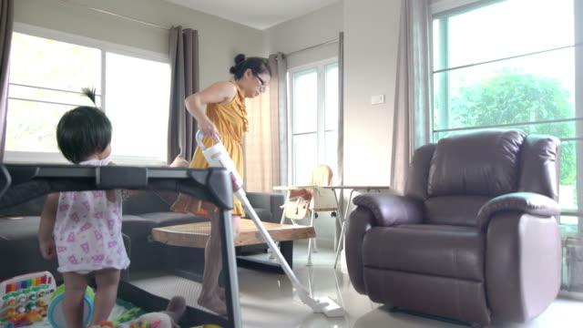 stockvideo's en b-roll-footage met aziatische moeder die door draadloze stofzuiger thuis schoonmaakt - east asian ethnicity