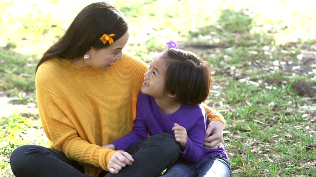 Asian mother, daughter in park talking, flower in hair