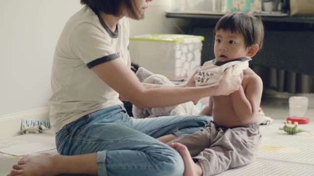 vídeos y material grabado en eventos de stock de asia madre vestido de niño en el hogar. - cambiar pañal