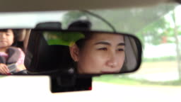 Asian Mother driving a car, having her little baby girl in a child seat