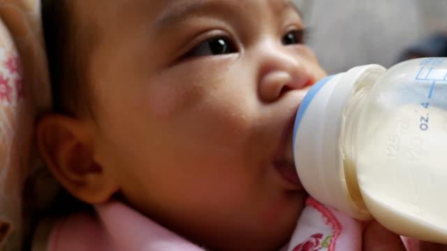 asiatische mutter füttert babymädchen aus flasche - füttern stock-videos und b-roll-filmmaterial