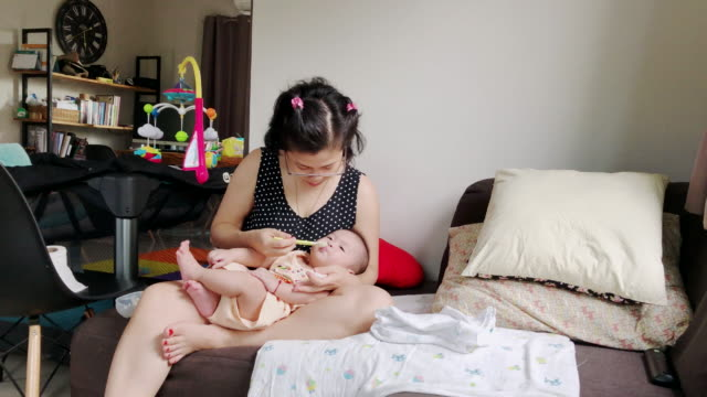 Asian mother feeding her baby son with a spoon while sitting on the sofa at home.