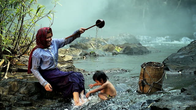 hd: asian mother giving a kid a bath in the waterfall. - village stock videos & royalty-free footage