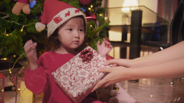 asian mother giving a present box or gift box to her daughter in christmas holiday while staying at home. cute toddler enjoy and happy with her x'mas present - christmas gift stock videos & royalty-free footage