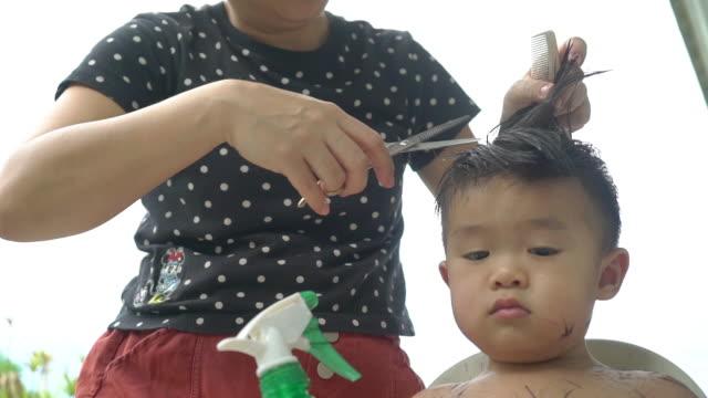 vídeos de stock e filmes b-roll de asian mother giving her son's haircut at home during quarantine. - estilo de cabelo