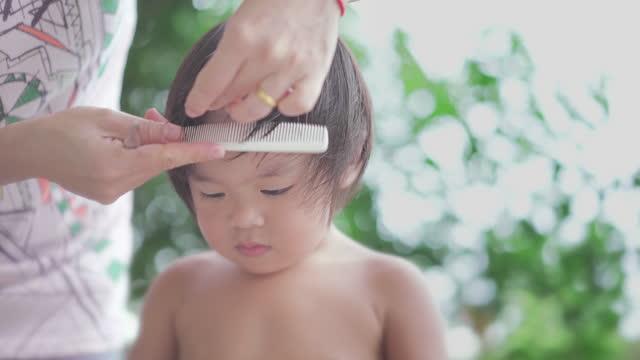 vidéos et rushes de cu mère asiatique donnant la coupe de cheveux de son fils à la maison - son