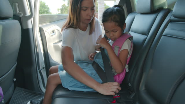 asian mother help her daughter fastening safety seat belt in car before go to school. get ready to school concept. - seat belt stock videos & royalty-free footage