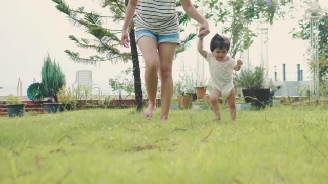 vídeos de stock, filmes e b-roll de mãe asiática ajuda a filha a aprender a andar - primeiros passos