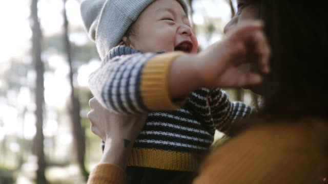 asian mother holding and kissing her baby boy - ridere video stock e b–roll
