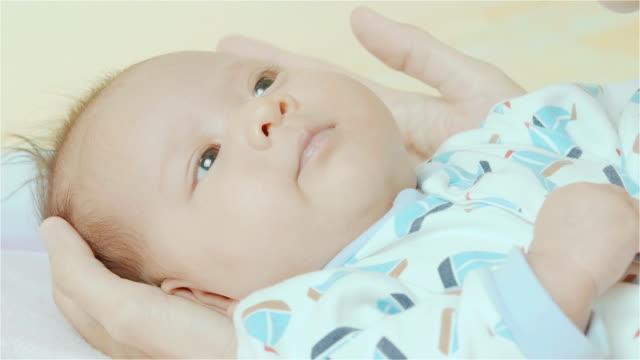 vídeos de stock e filmes b-roll de asiáticos mãe segurar e beijar na boca da sua raça mista fofinho pequena menina bebê recém-nascido em seu quarto - quarto do bebé