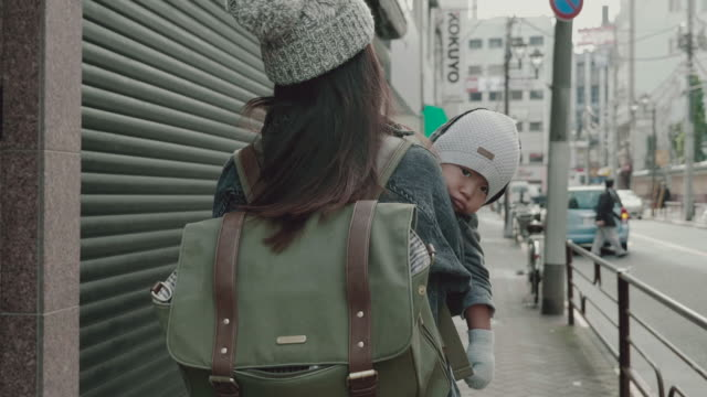 asian mother holding baby (12 months) boy and walking on the street. - randoseru stock videos & royalty-free footage