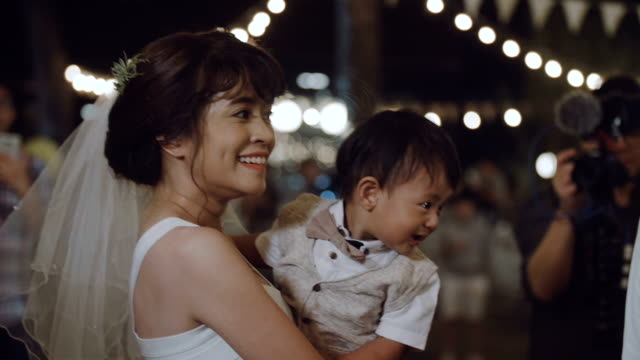 Asian mother holding baby boy in her wedding party at night.