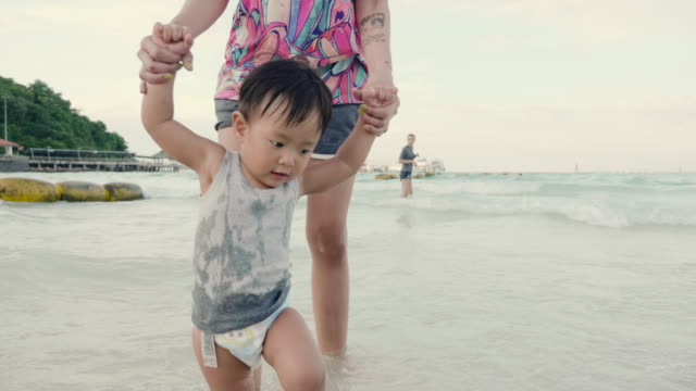 asian mother holding hand baby boy and walking on sea coast. - reportage stock videos & royalty-free footage