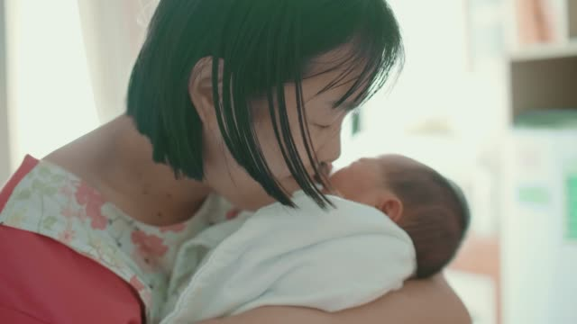 asian mother holding newborn in her arms and kissing - nursery bedroom stock videos & royalty-free footage