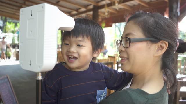 アジアの母親は、デジタル魔法瓶で体温を測定する彼女の息子を保持します - 温度計点の映像素材/bロール