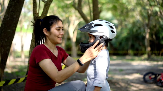 slo mo asian mother is putting safety helmet on his little son's head. - sports helmet stock videos & royalty-free footage
