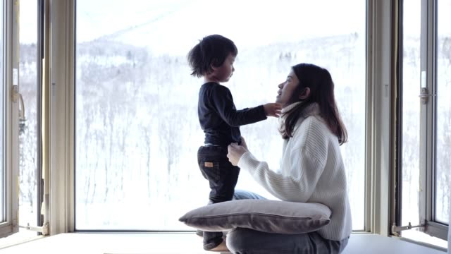 asian mother kissing and looking snow window cute little boys at home. - hokkaido stock videos & royalty-free footage