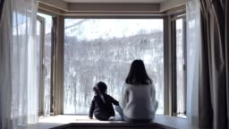 Asian mother kissing and looking snow window cute little boys at home.