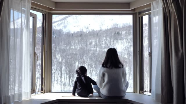 vídeos de stock e filmes b-roll de asian mother kissing and looking snow window cute little boys at home. - aconchegante