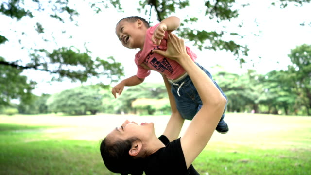 asian mother laughing and holding baby boy in the air. - toddler stock videos & royalty-free footage