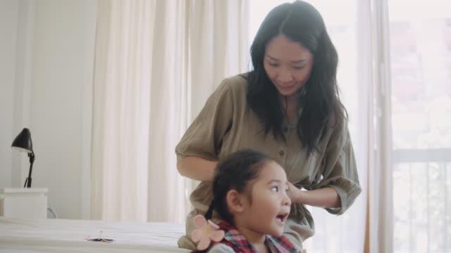 アジアの母親は、学校に準備ができて彼女の娘の編み込み髪を作ります。 - 初登校日点の映像素材/bロール