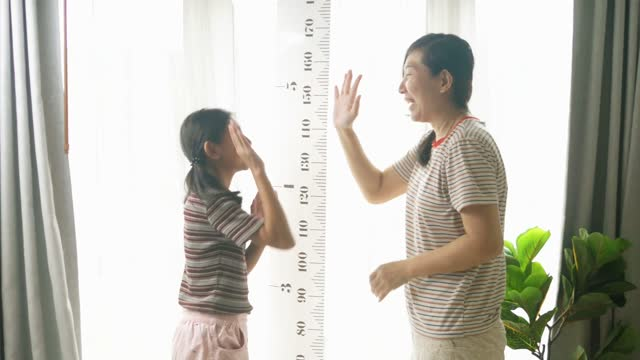 asian mother measures her daughter's height against the window, lifestyle concept. - moving image stock videos & royalty-free footage