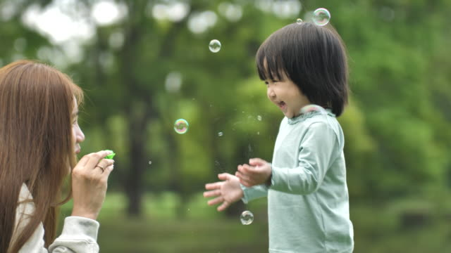 asian mother mother blows bubbles with the child,blowing soap bubbles, having fun in the park - asian and indian ethnicities stock videos & royalty-free footage
