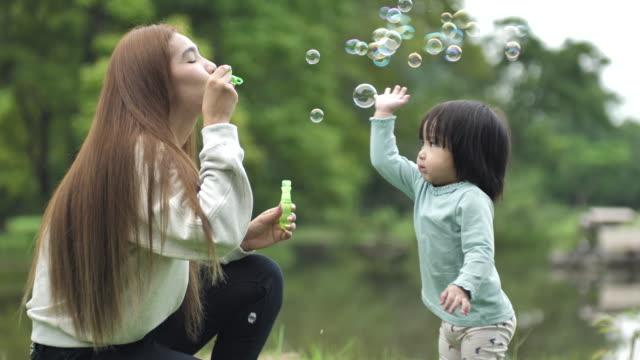 アジアの母母は子供と泡を吹く、石鹸の泡を吹いて、公園で楽しんで - 春点の映像素材/bロール