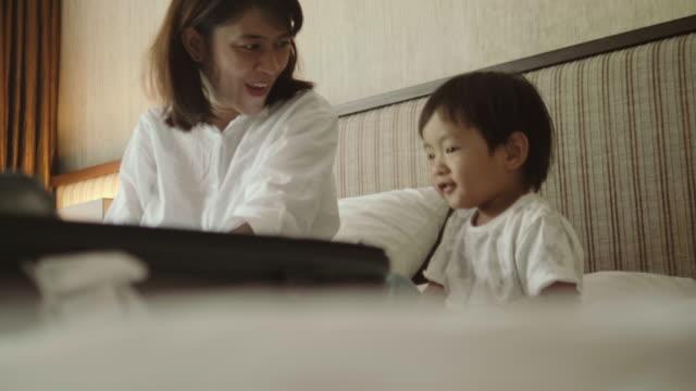 vídeos de stock, filmes e b-roll de mala de embalagem asiáticos mãe com seu filho. - bagagem