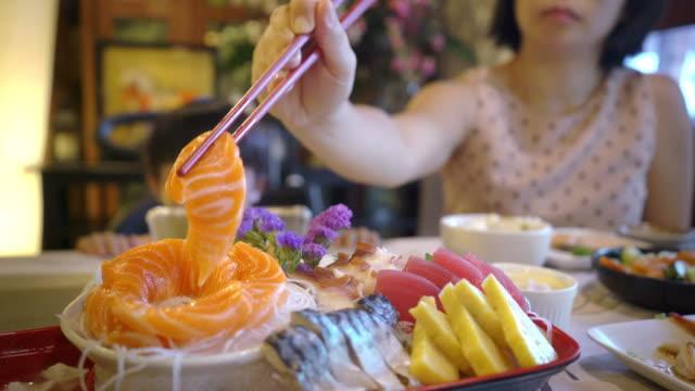 日本のレストランでスマートフォンからゲームをしながら息子の間に食べるためにサーモンの刺身を選ぶアジア人の母親。 - 生後18ヶ月から23ヶ月点の映像素材/bロール