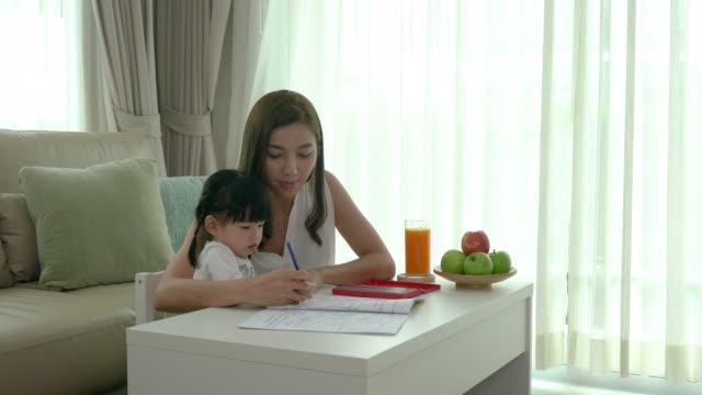 自宅のリビングルームのテーブルで色鉛筆と一緒に描く彼女の幼児と遊ぶアジアの母親。 - 鉛筆点の映像素材/bロール