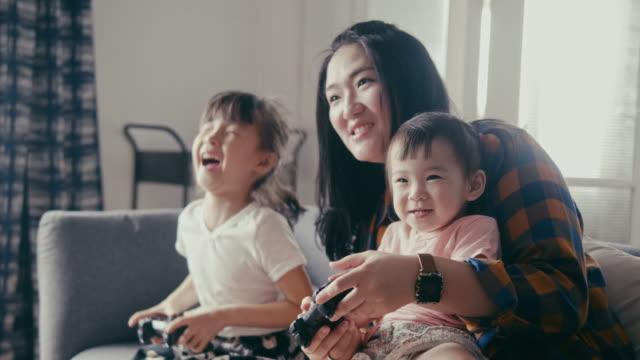 vidéos et rushes de la mère asiatique joue au jeu vidéo avec ses filles (mouvement lent) - famille avec deux enfants