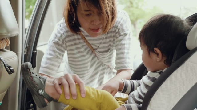 Asian Mother Putting Baby Son Into Car Seat