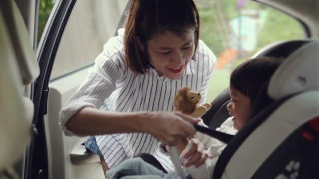 車旅行の座席に赤ちゃんの息子を置くアジアの母