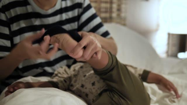 vídeos de stock, filmes e b-roll de asiática mãe vestir meias o filho na cama. - descalço