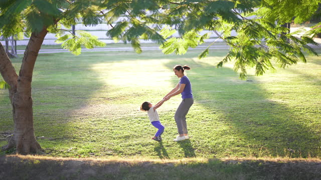 asian mother spinning her son in park, outdoor. - candid stock videos & royalty-free footage