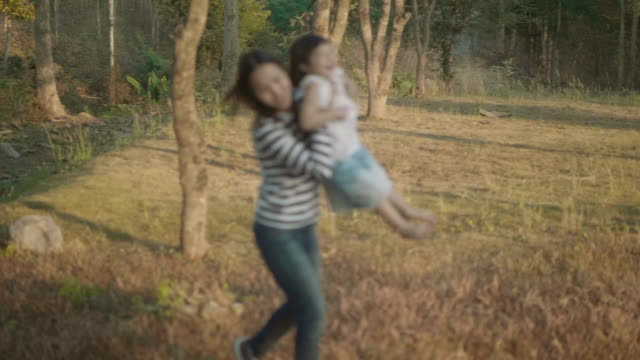 asian mother swinging girl in park slow motion - carrying stock videos & royalty-free footage