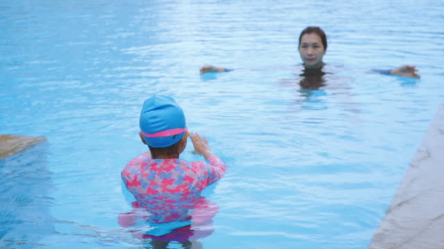 asian mother teaching daughter to swimming in pool, slow motion. - historical reenactment stock videos & royalty-free footage