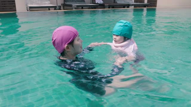Asiatische Mutter Lehre Tochter zum Schwimmen im Pool