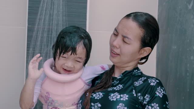 asiatische mutter lehre tochter zum schwimmen im pool - schwimmflügel stock-videos und b-roll-filmmaterial