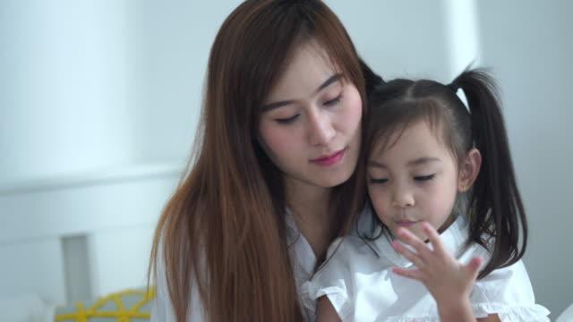 vídeos y material grabado en eventos de stock de madre asiática enseñando adola para contar el número con los dedos - doughter