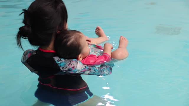 vidéos et rushes de asian mother teaching her baby to swim at swimming pool, floating - vêtement de bébé