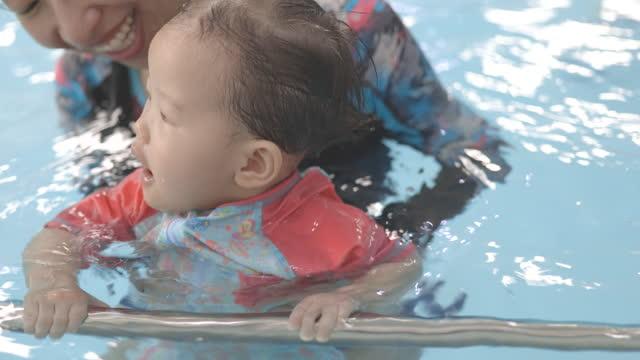 vidéos et rushes de asian mother teaching her baby to swim at swimming pool, holding on to safety railing - vêtement de bébé