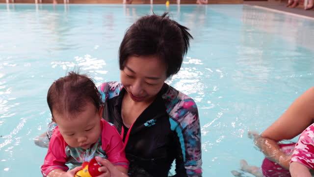 vidéos et rushes de asian mother teaching her baby to swim at swimming pool, playing with toy - vêtement de bébé