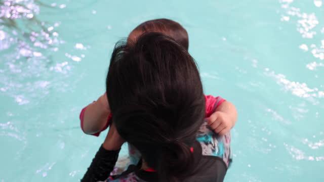 vidéos et rushes de asian mother teaching her baby to swim at swimming pool - vêtement de bébé