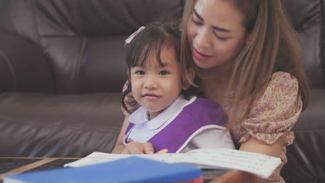 vídeos de stock e filmes b-roll de asian mother teaching her daugter homework reading and writing on notebook at living room.education concept,manual reader.4k dci footage. - soletrar