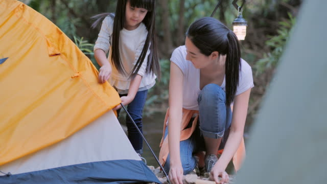 vídeos de stock, filmes e b-roll de mãe asiática ensinando a menina sobre sustentabilidade na floresta acampando. família feliz passando um tempo juntos ao ar livre. ensinando crianças sobre sustentabilidade - ecossistema